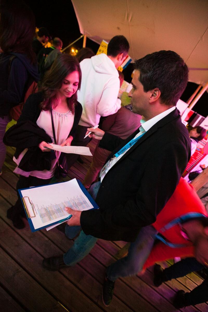 Un homme explique quelque chose à une jeune fille tenant un papier.