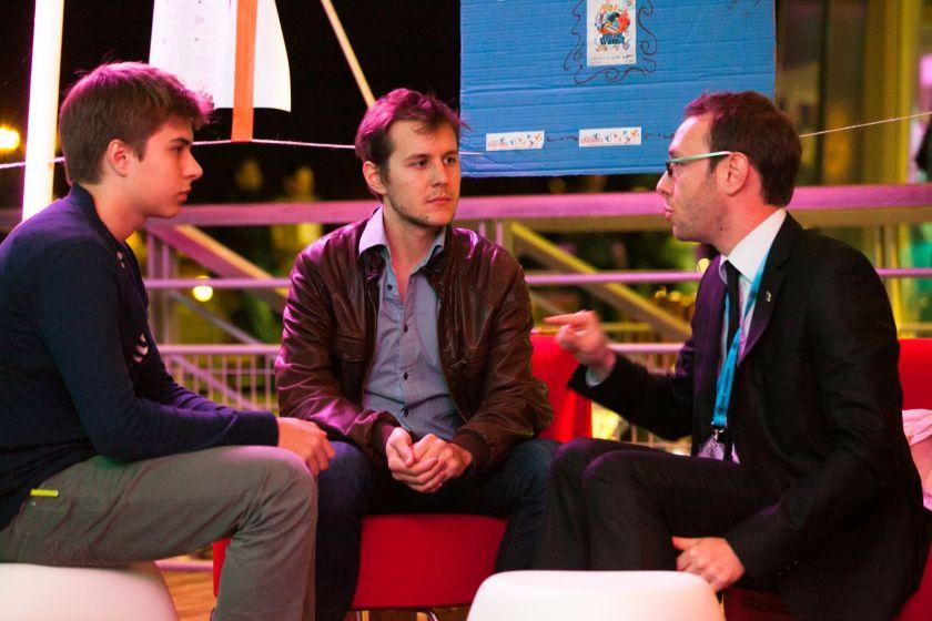 Présentation des associations : trois jeunes hommes discutent assis.
