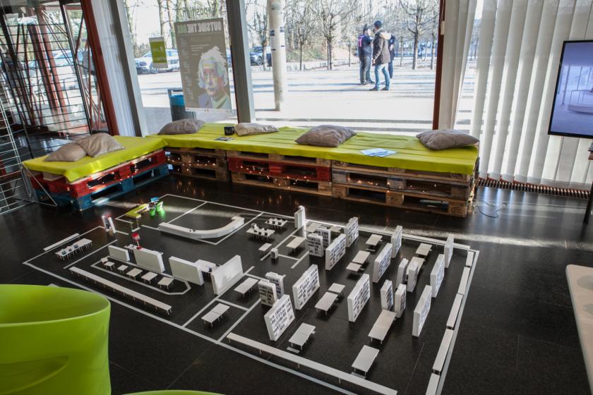 Une maquette en papier de la bibliothèque universitaire, des bancs et des coussins.
