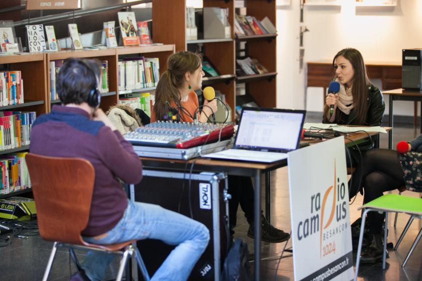 Un plateau radio avec trois personnes installé dans une bibliothèque