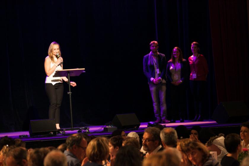 Anne-Emmanuelle Grossi avec un micro sur la scène du CLA.