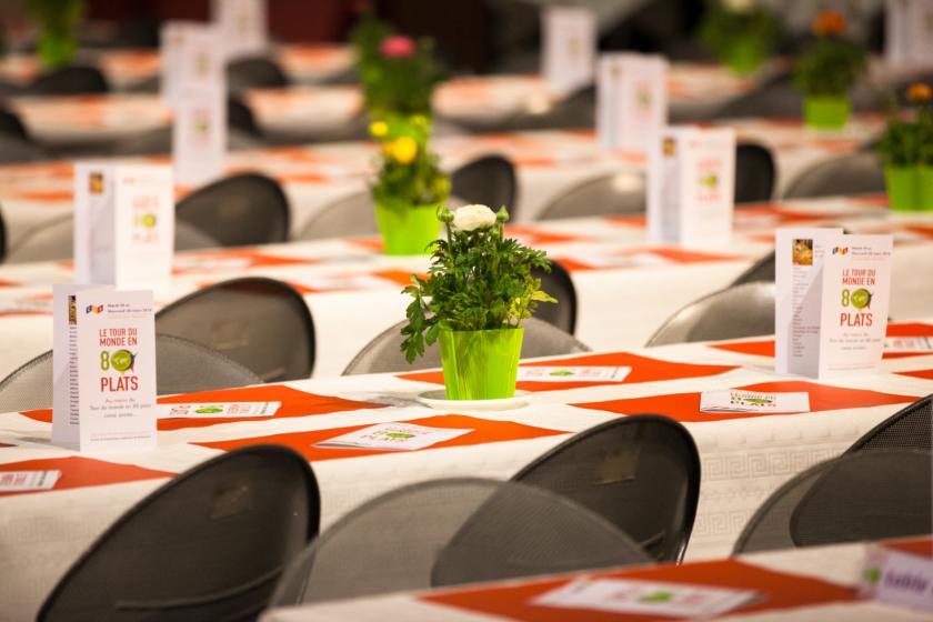 Des rangées de tables décorées avec des fleurs et le menu du tour du monde en 80 plats.