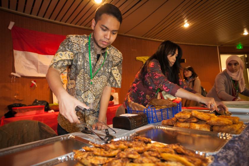 Deux malaisiens déposent de la nourriture sur des plats.