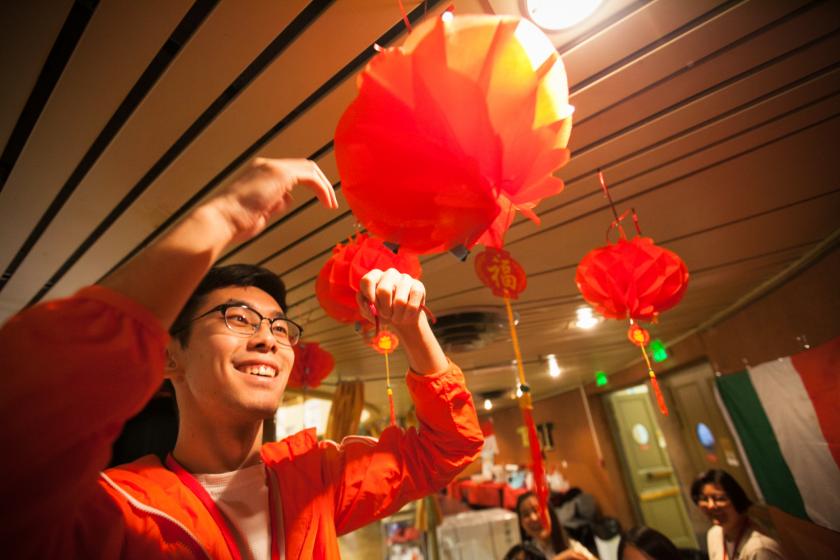 Un jeune chinois installe au plafond des boules de papier colorées.