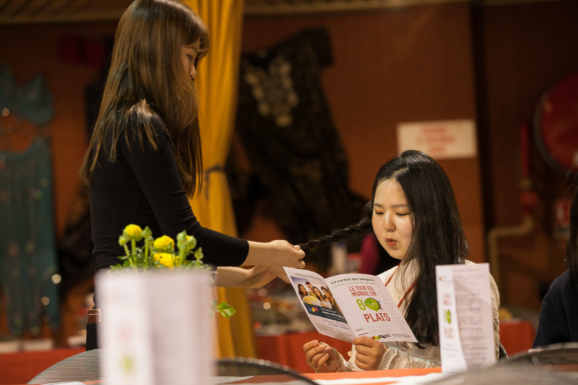 Une jeune fille debout fait des nattes à une jeune fille assise qui lit le menu du tour du monde en 80 plats.