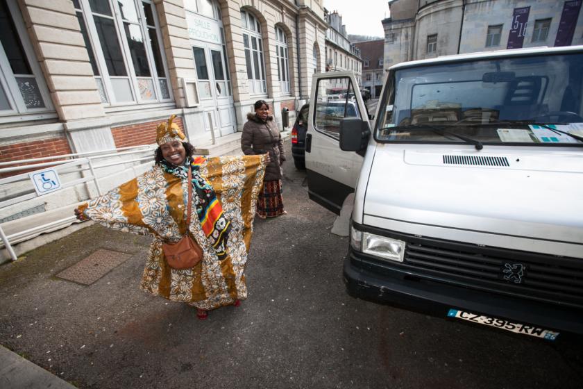 Une dame sénégalaise souriante en boubou sort d'un camion.