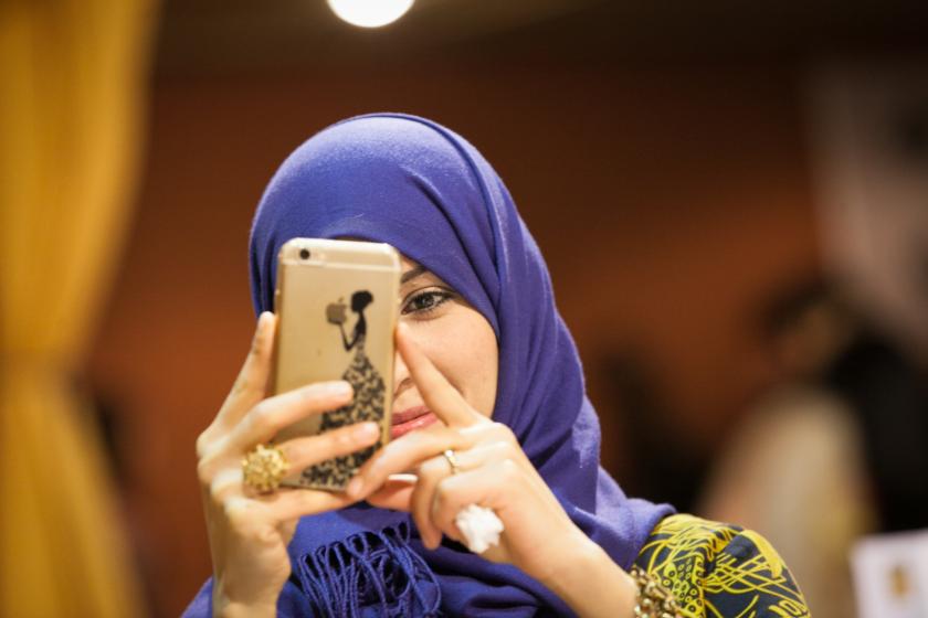 Une femme portant un foulard violet en train de prendre une photo avec son téléphone portable en souriant.
