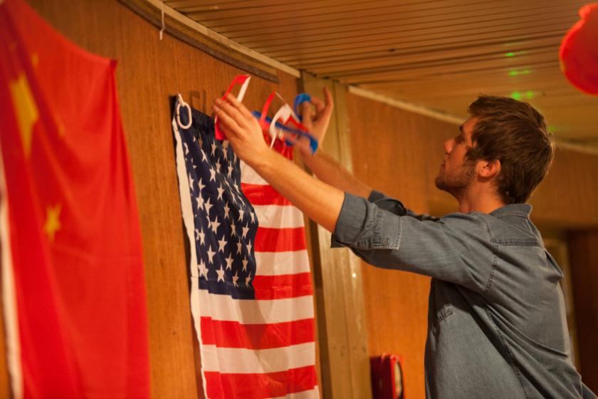 Un jeune homme accroche quelque chose au dessus d'un drapeau américain.