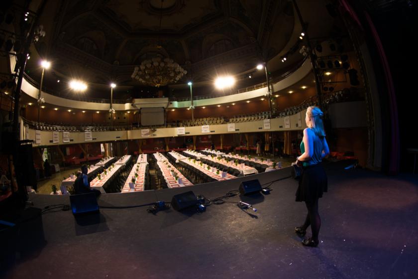 une jeune fille blonde de dos sur une scène face à une salle vide