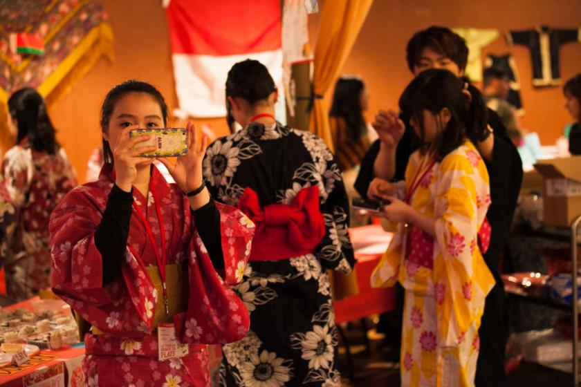 Plusieurs jeunes japonais en kimono. Une jeune fille prend une photo avec son téléphone portable. Un jeune homme ajuste la coiffure d'une autre.