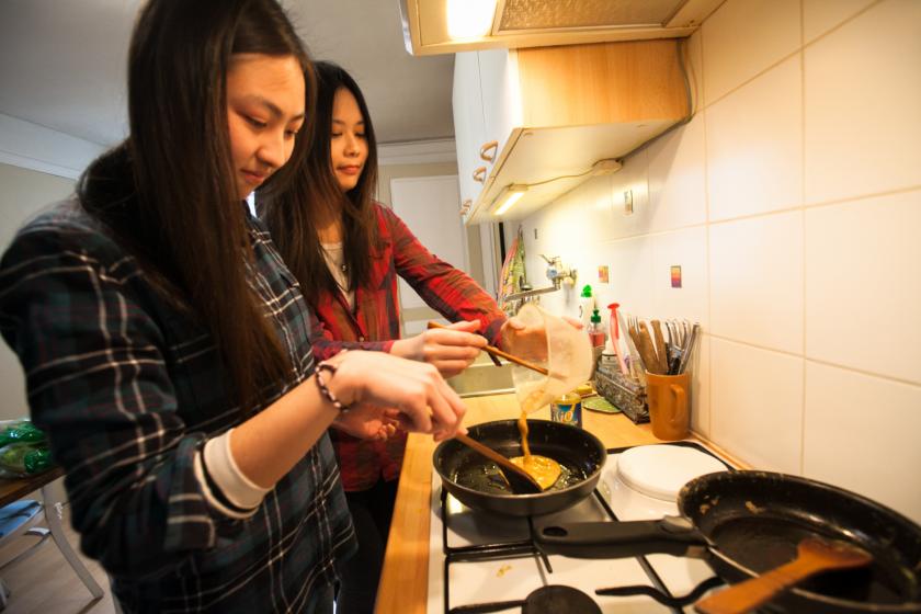 Deux étudiantes taïwanaises en train de mettre une omelette dans une poele.