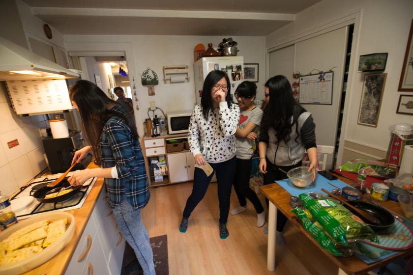 Quatre jeune tawanaises dans une cuisine en train de préparer des omelettes et de la salade.