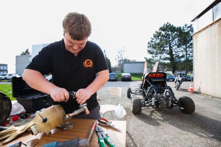 Un éudiant en train de faire de la mécanique à l'extérieur de l'IUT. Un kart en arrière plan.