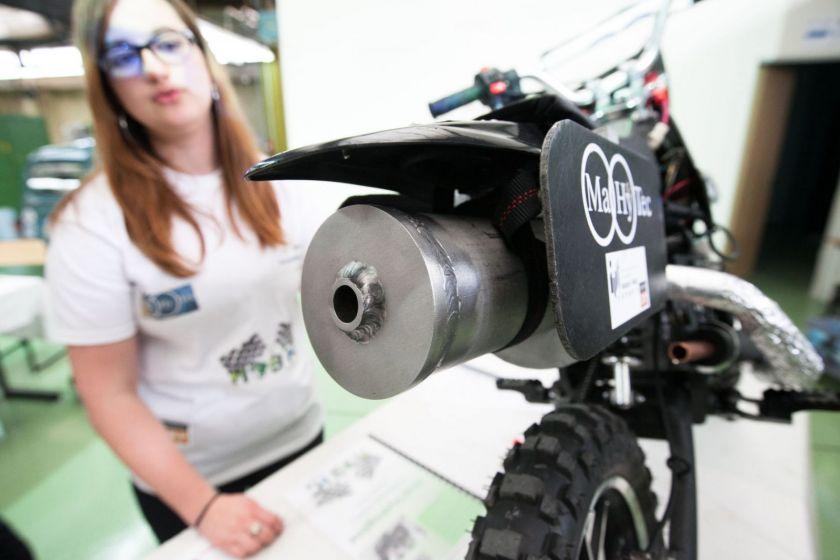 Arrière d'une moto à hydrogène. une étudiante en arrière-plan explique son fonctionnement.