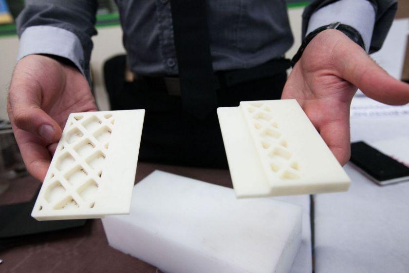 Deux mains montrent des pièces mécaniques faites à l'imprimante 3D.