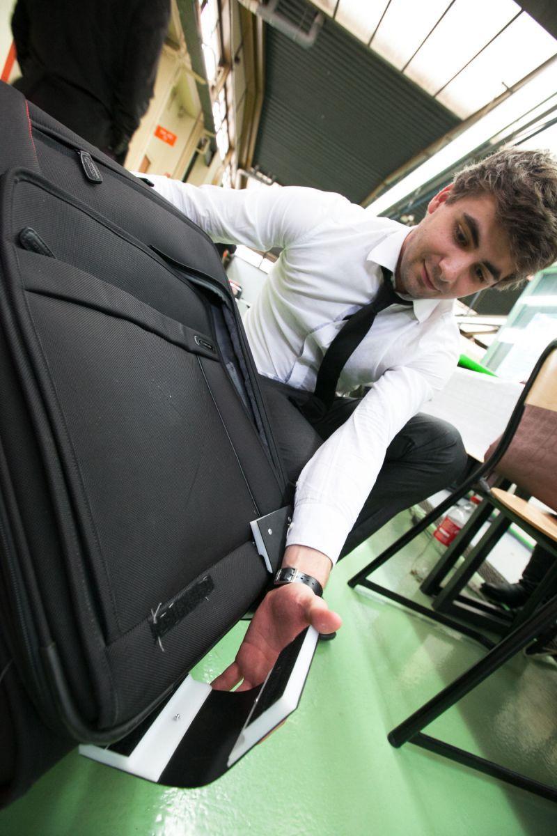 Un étudiant en chemise et cravate fixe une pièce sur une valise.