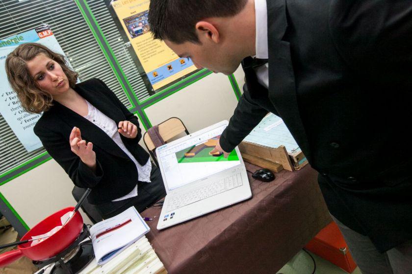 Une étudiante et un étudiant présentent quelque chose sur un ordinateur