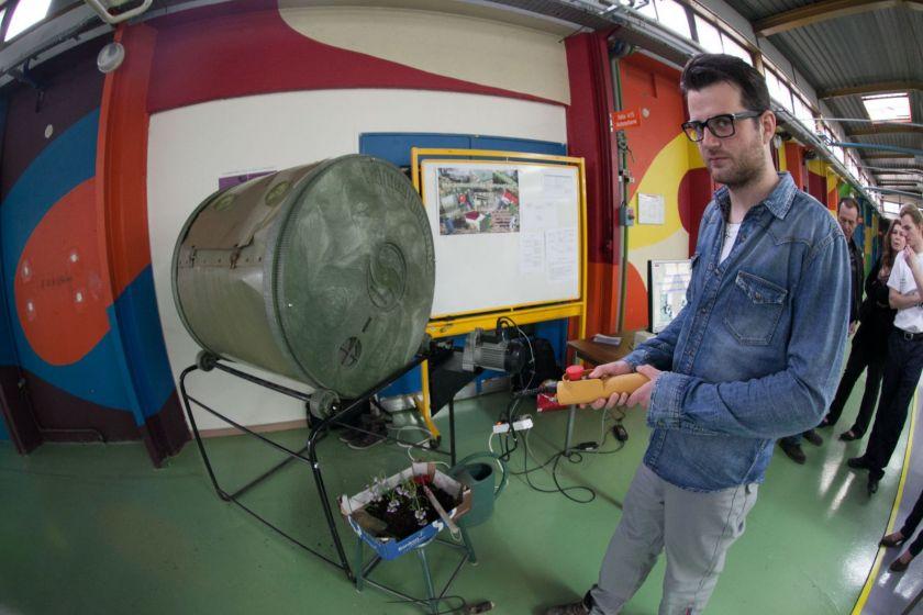 Un étudiant présente une machine à compost.