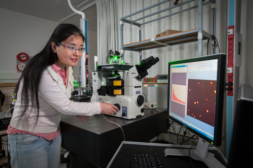 Une jeune femme asiatique manipule un dispositif optique en souriant. Beaucoup d'appareillages autour d'elle.
