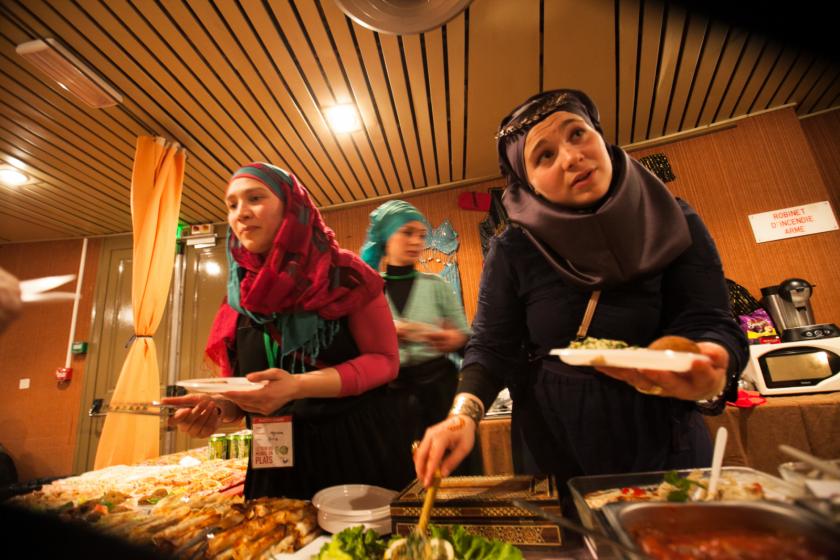 Trois femmes portant le vioile devant un stand en train de servir de la nourriture aux visiteurs?