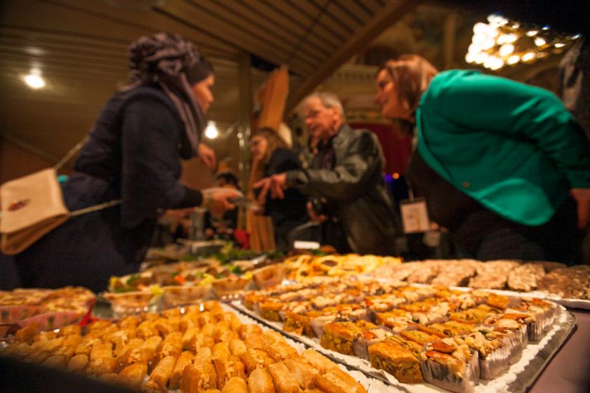 Une table pleine de pâtisseries orientales avec des personnes floues en arrière-plan.
