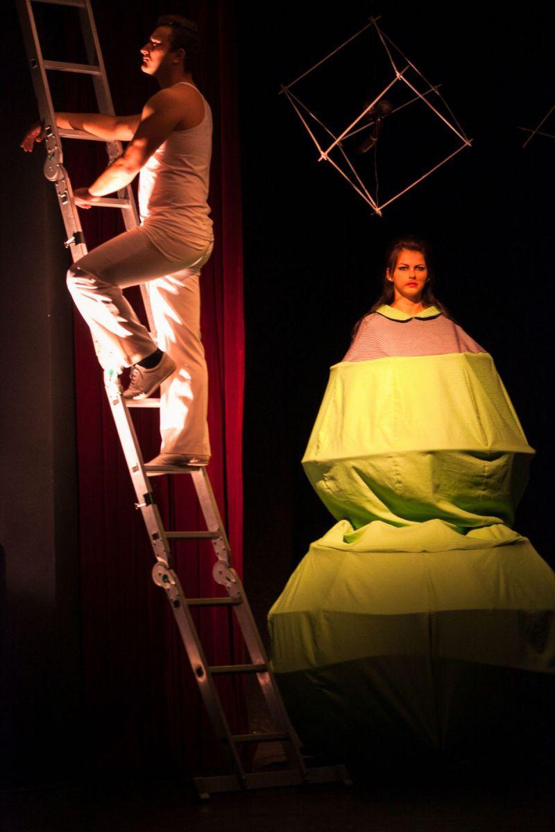 Scène de théâtre : une homme grimpe sur une échelle et une femme est immobile dans une sorte de grosse boule verte.