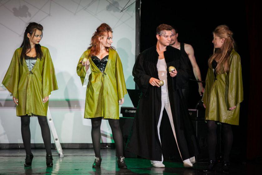 Scène de théâtre : un homme en manteau noir avec une couronne donne des pommes à trois jeunes femmes en blouse verte.
