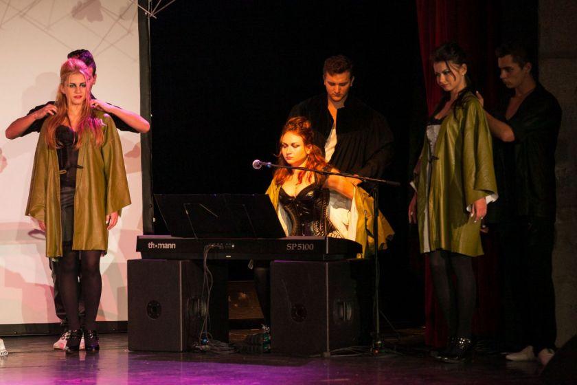 Scène de théâtre : trois jeunes hommes habillent trois jeunes femmes d'une blouse verte. L'une est installée à un clavier.