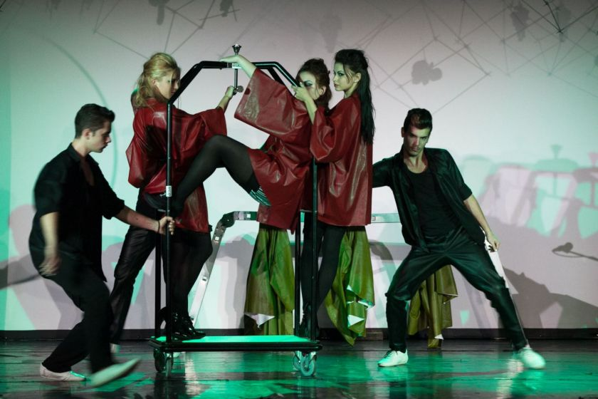 Scène de théâtre : 3 jeunes femmes perchées sur un porte-manteau à roulettes tiré par deux jeunes hommes.