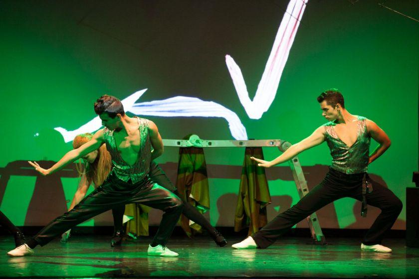 Deux hommes dansent sous un éclairage vert.