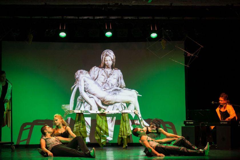 Deux couples sur scène imitent la pose d'une sculpture projetée sur l'écran derrière eux.