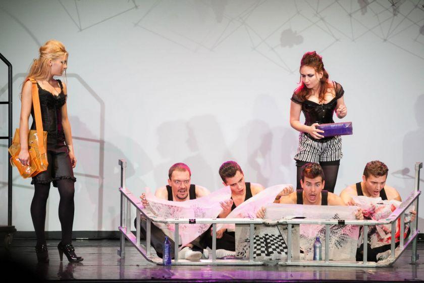 Deux jeunes femmes debout regardent quatre jeunes hommes assis qui lisent des journaux en faisant des mimiques exagérées.