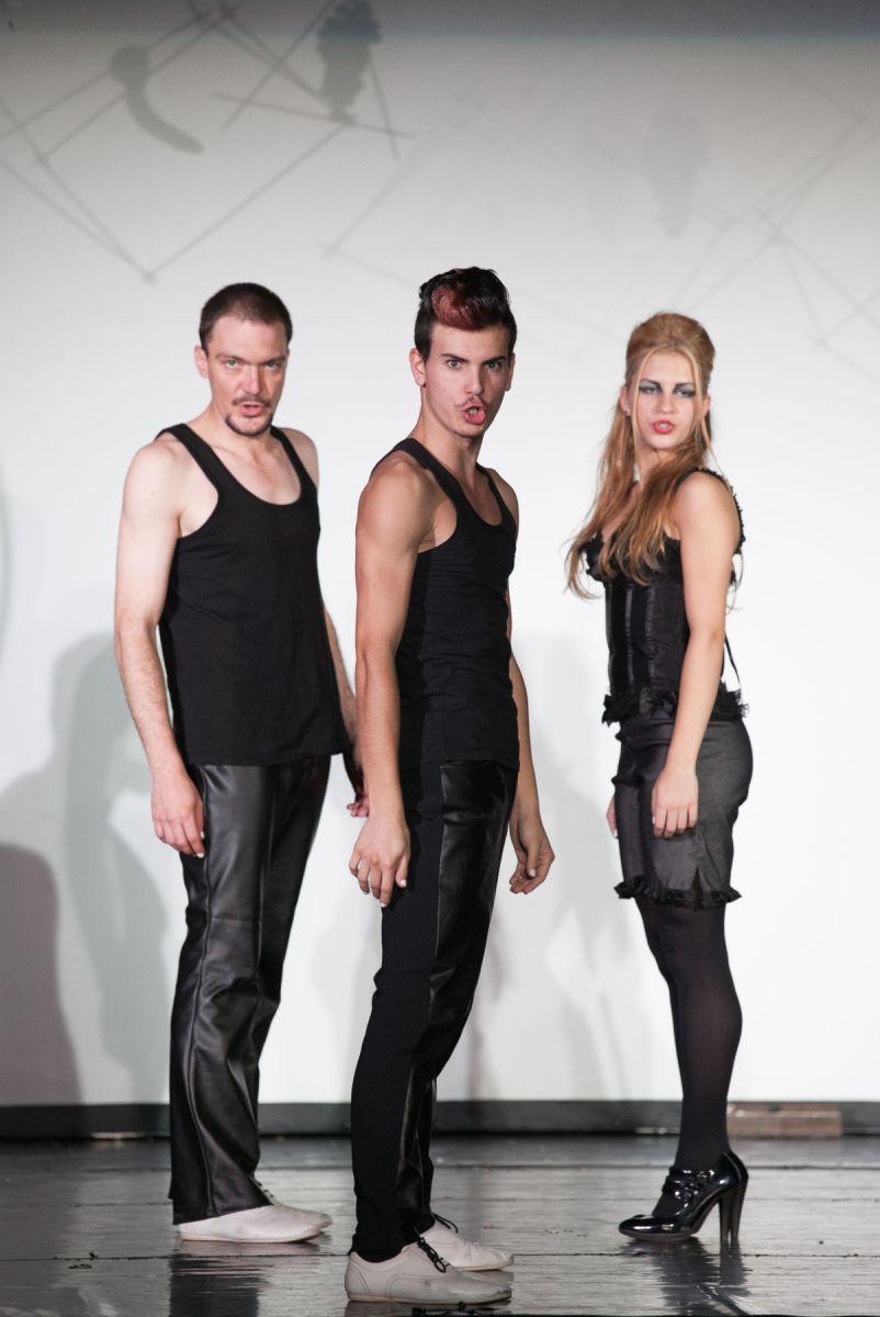 Scène de théâtre : deux jeunes hommes et une jeune femme se tiennent debout et parlent.
