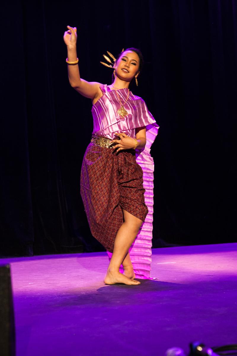 Une jeune fille en costume traditionel thailandais exécute une danse.
