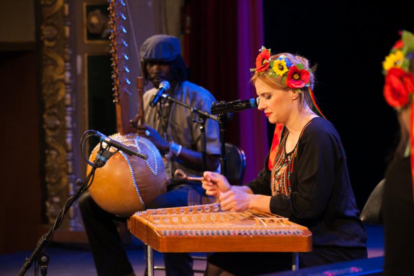 Une jeune femme biélorusse en costume joue du cymbalum.