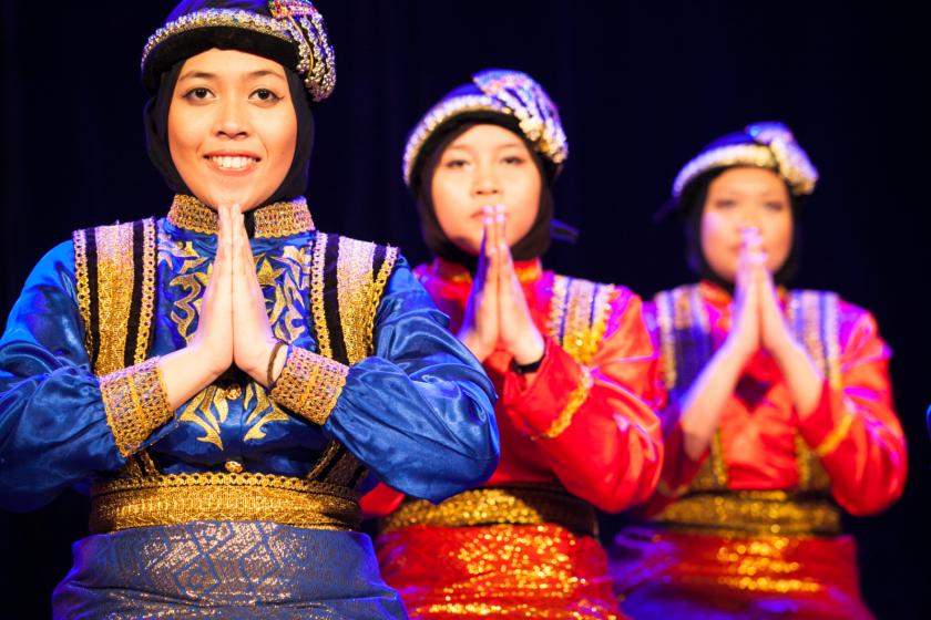 Trois jeunes femmes indonésiennes en costume traditionnelle exécutent une danse.