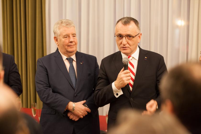 Deux hommes en cravate dont l'un tient un micro
