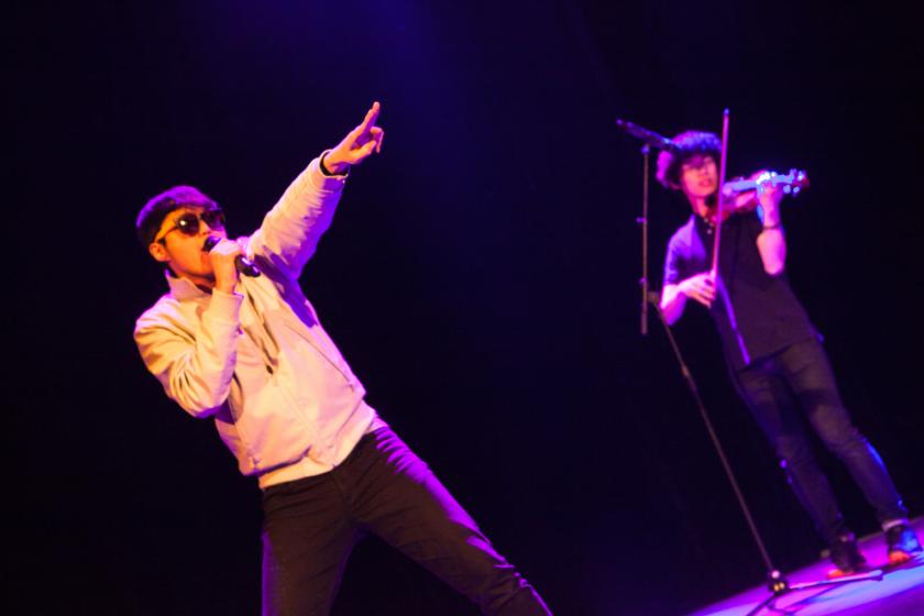 deux étudiants coréens sur une scène, l'un au micro, l'autre au violon