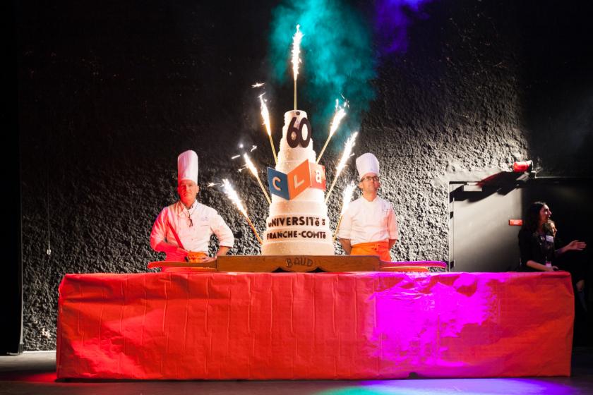 Un gateau à étages avec deux chefs cuisiniers en toque de chaque côté.
