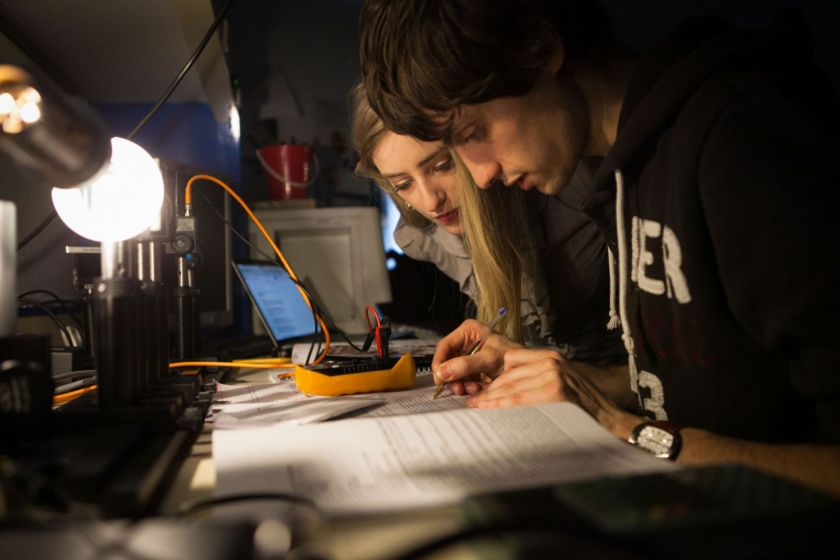 Un étudiant et une étudiante penchés sur un même document.