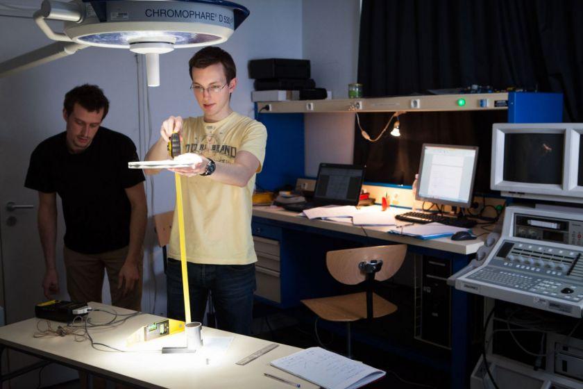 Deux étudiants dans une salle de TP, l'un tient un disque d'une main et un mètre ruban.