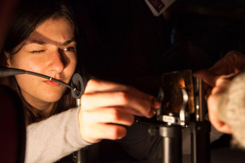 Une étudiante, en gros plan, un oeil fermé, effectue un réglage sur un appareil optique.