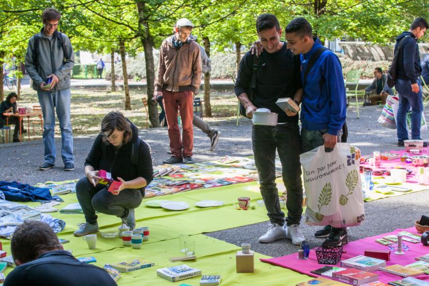 Image de brocante : des jeunes gens en train d'inspecter des objets disposés par terre sur des nappes.