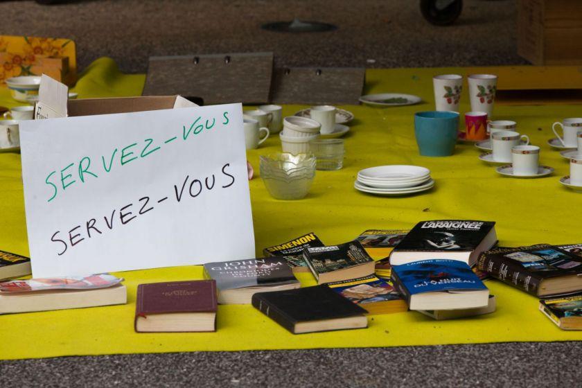"""Des affaires (livres, vaisselle) posés au sol avec un écriteau """"servez-vous"""""""