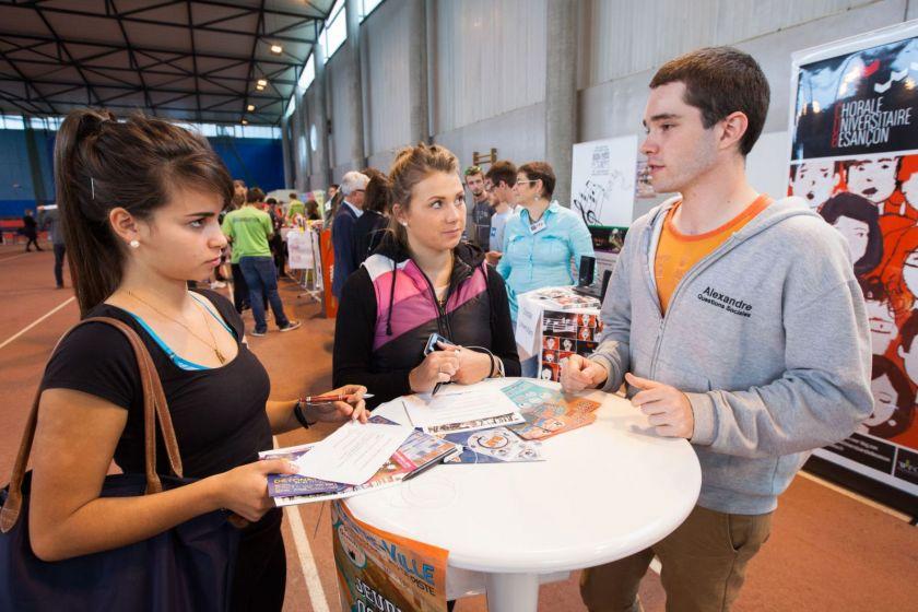 Un étudiant discute avec deux étudiantes autour d'une table.