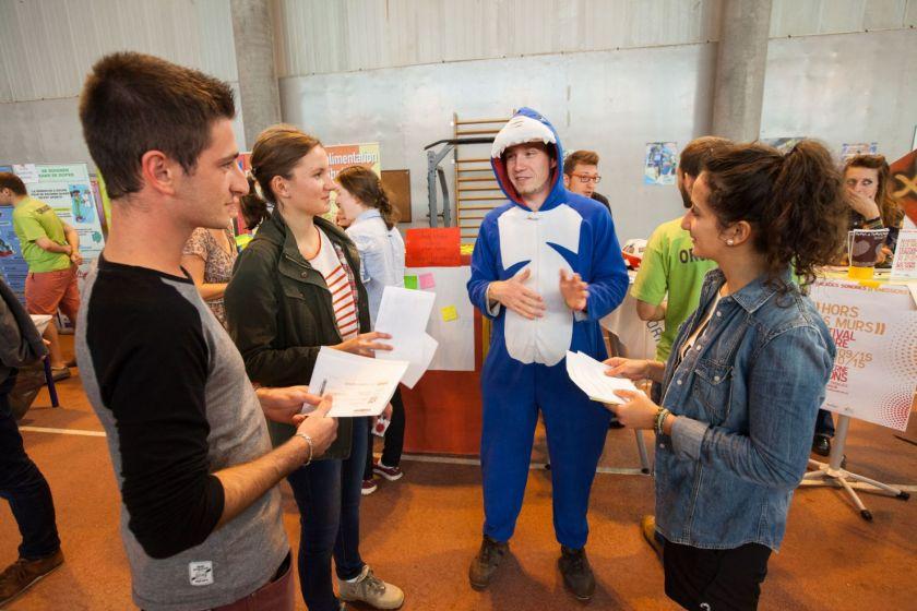 Un jeune homme déguisé parle avec trois étudiants.