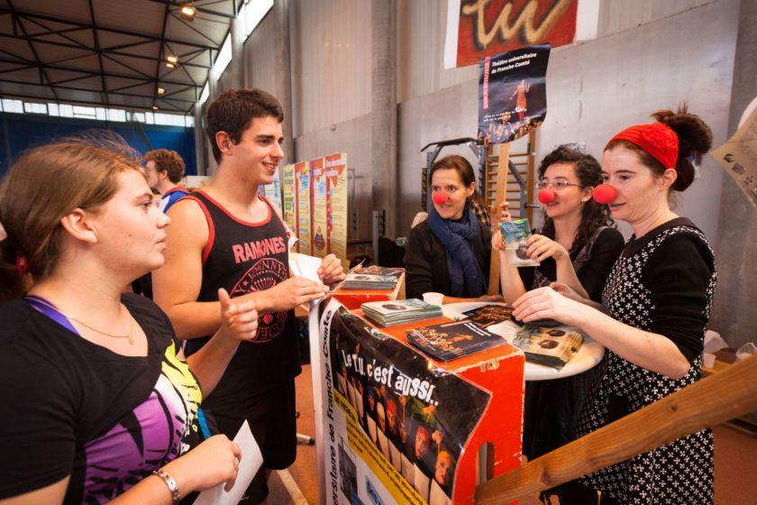 Plusieurs jeunes femmes portant un nez rouge de clown en train de discuter avec des étudiants sur un stand.