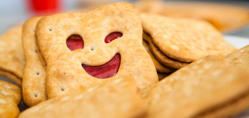 Une série de biscuits fourrés en gros plan dont un biscuit en forme de visage qui fait un clin d'oeil.