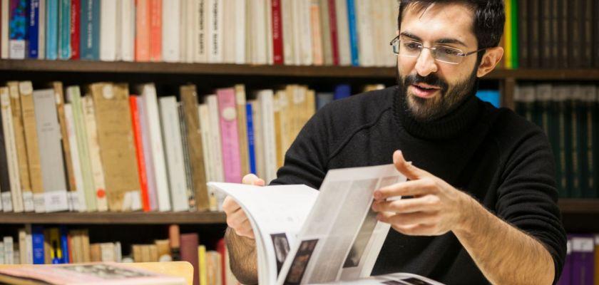 Anton Alvar Nuno feuillette un livre. Une bibliothèque en fond.