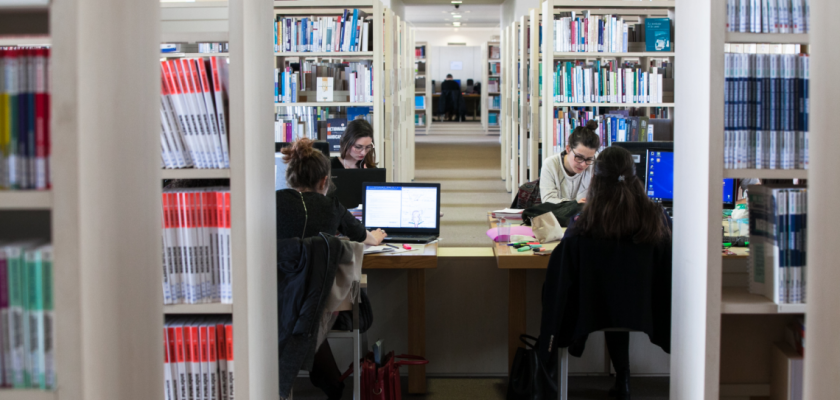 Vue intérieure de la BU Santé avec des rayonnages de livres et des étudiantes qui travaillent sur des ordinateurs.